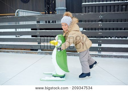 Little girl with toy penguin skating on ice rink alone