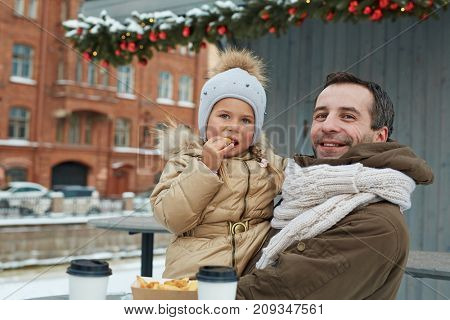 Hungry girl eating french fries on her father hands outdoors