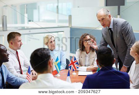 Mature deputy explaining his viewpoint to representatives of various countries at summit