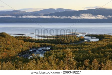 September morning in the Nordic mountains. Sunrise, river, lake and mountains. Some fog over the lake.