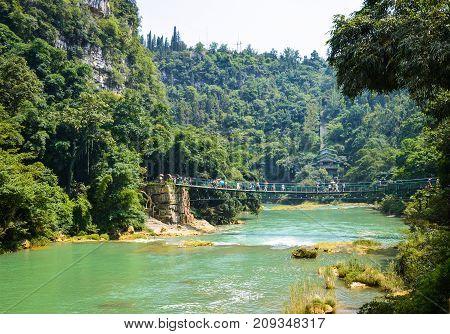 Beautiful scene of forest river and suspension bridge in China Guizhou Huangguoshu scenery park.