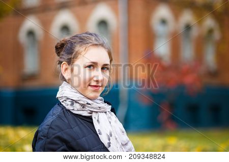 Young female student standing near college building in autumn. Education background with student girl and copy space
