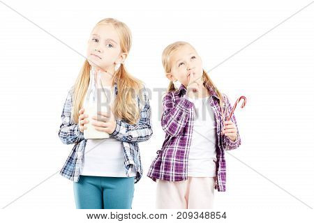 Studio portrait of two little sisters holding bottle of milk and candy cane