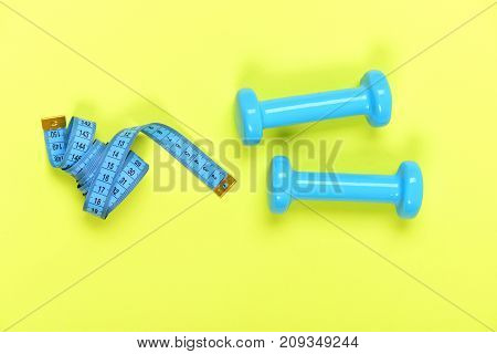 Dumbbells And Measure Tape In Cyan Color On Light Yellow
