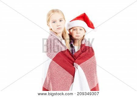 Studio portrait of two little sisters wrapped in blanket and wearing Santa hat