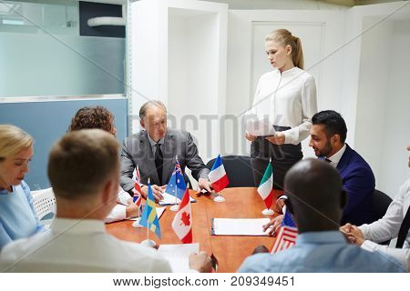 Young female delegate making report for colleagues during conference