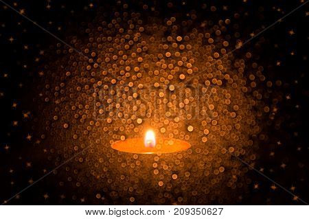 Candle in glass with bokeh. Background with bokeh