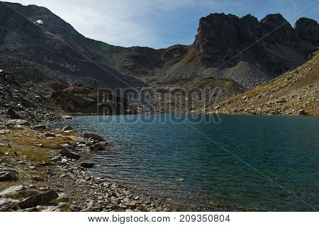 landscape of a high mountain lake with daylight with translucent stones through the water at the bottom of the lake and sharp rocks in the background. High-altitude lake in arkhyz. North Caucasus