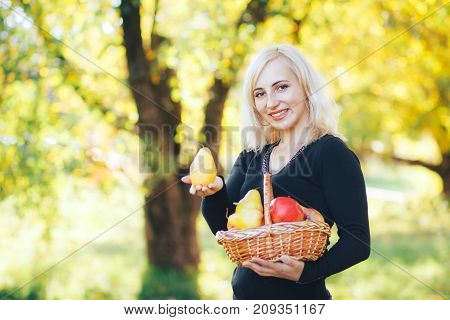 smiling blonde holding a beautiful pear and a basket of fruit.