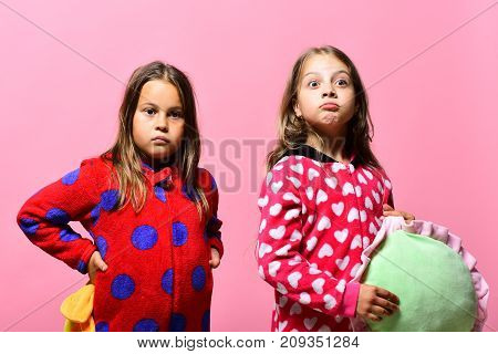 Kids With Surprised Faces Hold Green And Yellow Pillows