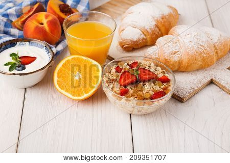 Traditional french breakfast menu . Yogurt with fresh berries, glass of orange juice, muesli and croissants on wooden table, copy space