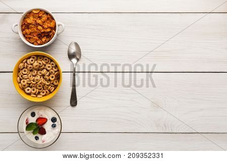 Healthy breakfast meals on wooden table copy space. Cereal rings, cornflakes and yogurt with berries and spoon, top view