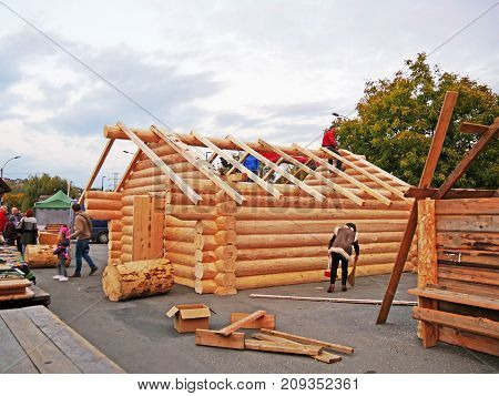 CLUJ-NAPOCA ROMANIA - OCTOBER 13 2017: Log cabin building in progress. Carpenters assemble timber frame with common rafters on cabin roof. worjing on the cabin roof structure assembling square timber rafters Carpenters lifting square timber rafters to the