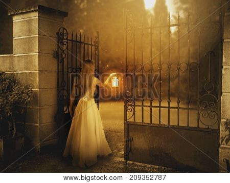 Young woman standing by the gate in sunrise with lantern