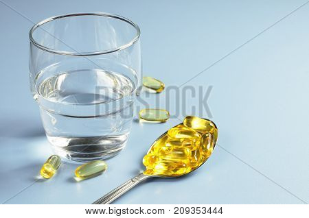 Fish oil omega 3 capsules in spoon and glass with water on blue table. Medicine concept