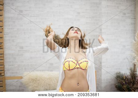 Woman in sexy yellow swimsuit poses in bedroom.