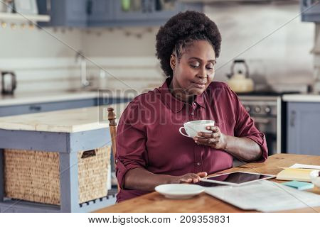 Smiling young African woman sitting alone at her kitchen table at home drinking coffee and working on a digital tablet