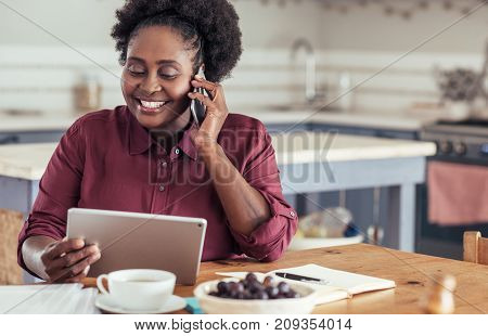 Smiling young African woman talking on a cellphone and using a digital tablet while sitting at a table working from home