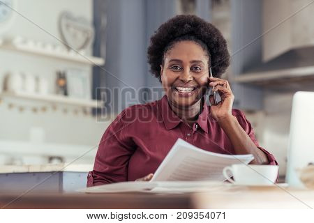 Portrait of a smiling young African woman talking on a cellphone and reading documents while sitting at a table working from home