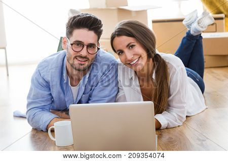 Beautiful Young Couple Using Laptop In Their New Home.