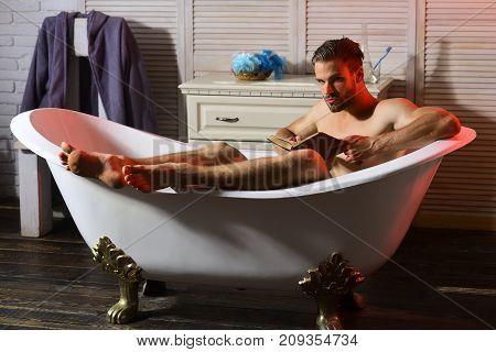 Macho With Suspicious Look Reading Book In Bathtub