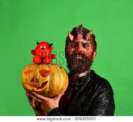 Demon With Horns And Proud Face Holds Carved Jack Lantern