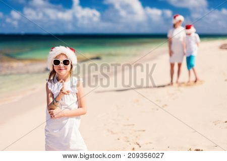 Happy beautiful family in red Santa hats on a tropical beach celebrating Christmas