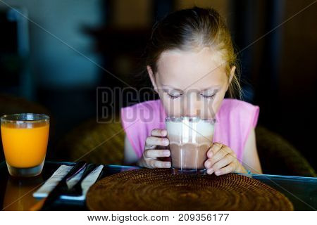 Adorable little girl in restaurant drinking hot chocolate