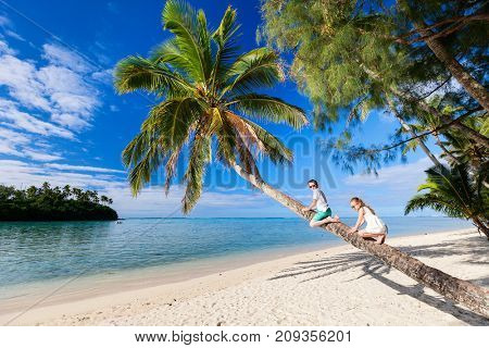 Kids at tropical beach sitting on palm tree during summer vacation