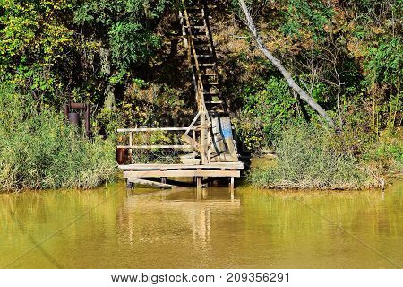 An old wooden staircase leads to the river bank.