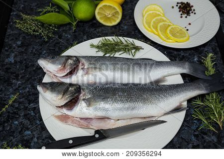 Raw seabass lies on a white plate with rosemary and lemon.