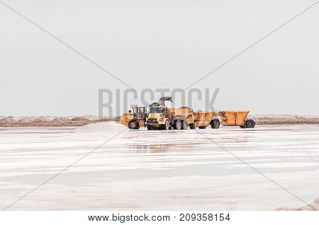 WALVIS BAY NAMIBIA - JULY 1 2017: Salt being loaded onto a truck at a salt lake at Walvis Bay in the Namib Desert on the Atlantic Coast of Namibia