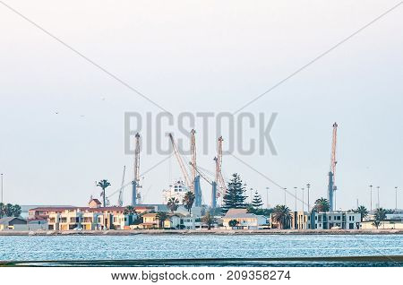 WALVIS BAY NAMIBIA - JULY 1 2017: A view of buildings accross the lagoon in Walvis Bay with the harbor in the back