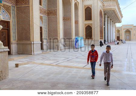 Fars Province Shiraz Iran - 19 april 2017: Shah Cheragh Shrine Two Iranian teenagers cross the courtyard of the mosque.