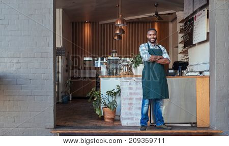 Portrait of a handsome young African entrepreneur smiling and standing welcomingly in front of the counter of his trendy cafe