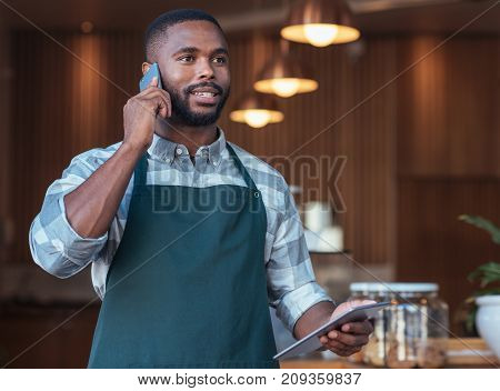 Smiling young African entrepreneur standing in his cafe talking on a cellphone and using a digital tablet