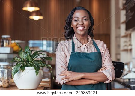 Portrait of a smiling young African female entrepreneur standing with her arms crossed in her trendy cafe