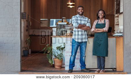 Portrait of two smiling young African entrepreneurs standing welcomingly together at the counter of their trendy cafe