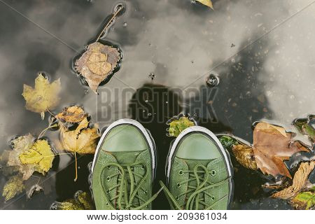 Top view of legs close-up in green sneakers standing in a puddle with yellow leaves in autumn in park
