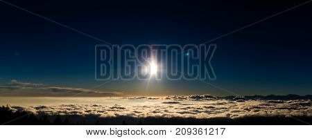 The sun setting on a sea of clouds.