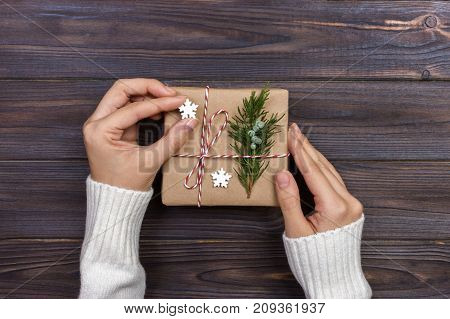 Hands of woman decorating Christmas gift box.