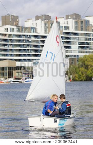 MOSCOW - SEP 16, 2017: Boy and his trainer sail on small yacht in Yacht club on Voykovskaya