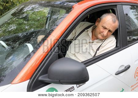 MOSCOW - SEP 17, 2017: Elderly man (wirh MR) in car of Moscow carsharing, сarshring is kind of short-term car rental. Carriage allows you to return car at any of points of service