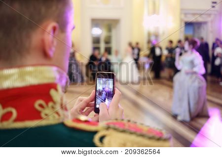 MOSCOW - SEP 16, 2017: Man shoots with smartphone during Great Catherine Ball (dance party) in Tsaritsyno