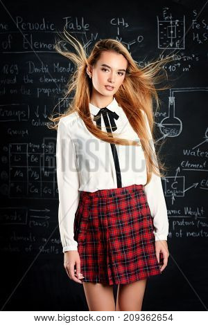 Pretty student girl with long blonde hair posing in school clothes by the chalkboard.