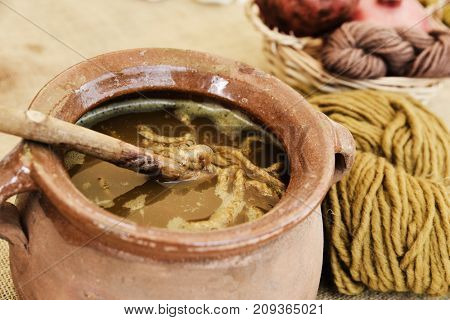 closeup of an earthenware pot where some skeins of wool are being dyed by the traditional process