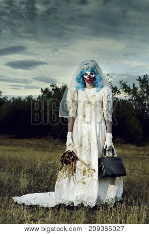 a scary evil clown wearing a dirty and ragged bride dress, and holding a bridal bouquet with wilted flowers and an old purse, in a disturbing rural landscape at dusk