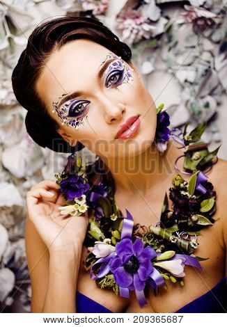 floral face art with anemone in jewelry, sensual young brunette woman in studio close up, 8 march concept