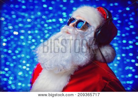 DJ Santa Claus in sunglasses and headphones. Christmas songs and music. Disco lights in the background.