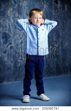 Five year old boy smiling at camera. Childhood. Kid's fashion. Full length portrait.
